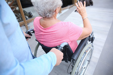 Senior woman in wheelchair and her husband on ramp outdoors