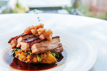 Braised pork belly in brown sauce with vegetables, modern Chinese cuisine in fine dining restaurant.