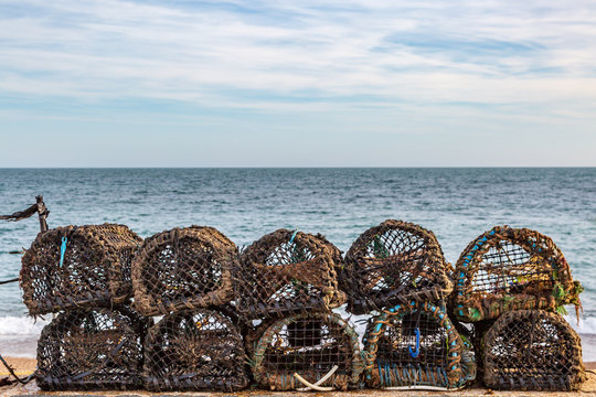 Lobster pots lined up on a beach, on the Isle of Wight