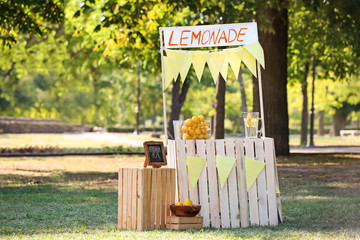 Wooden lemonade stand in park on sunny summer day