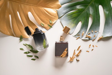 Bottles with perfumes and tropical leaves on light background Fototapete