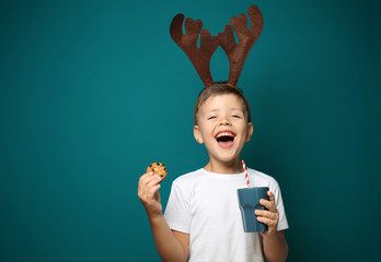 Cute little boy with toy reindeer horns holding cup of hot chocolate and cookie on color background