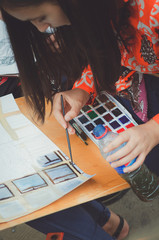 A teenager girl paints a picture with watercolors.