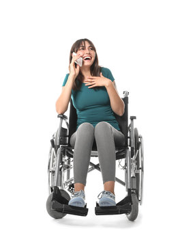 Young woman in wheelchair talking by mobile phone on white background