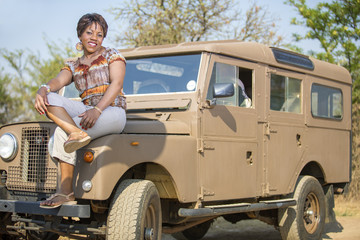 African woman sitting on a  vintage Land Rover.