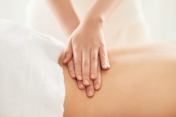 Crop hands of female therapist rubbing loin of female client during massage session in spa salon