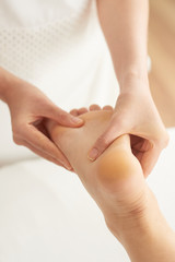 Close-up shot of hand rubbing foot of female client while doing massage in nice spa salon