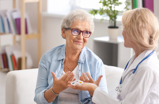 Doctor giving medicine to senior woman at home