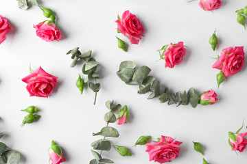 Composition with beautiful blooming flowers and leaves on white background