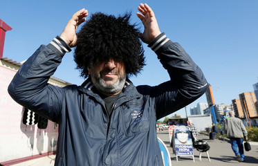A customer tries on a Caucasian sheepskin hat at a street market in Krasnoyarsk