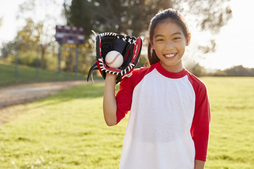Young Chinese girl holding baseball in mitt looks to camera