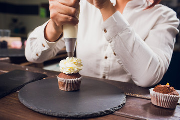 Woman making cream cheese top on cupcakes in kitchen. Cooking cakes.