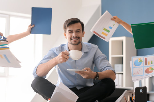 Businessman with a lot of work to do relaxing in office