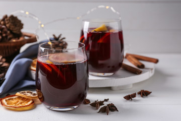 Glasses of delicious hot mulled wine on light table
