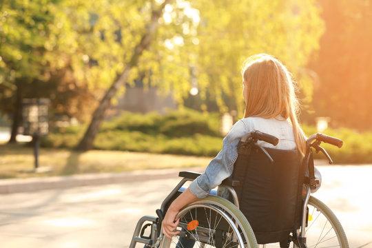 Cute teenage girl in wheelchair outdoors