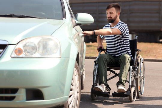 Man in wheelchair trying to open his car