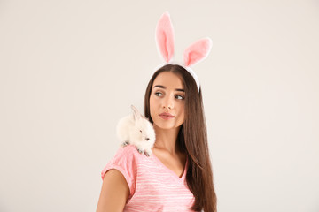 Beautiful young woman with bunny ears and cute rabbit on light background
