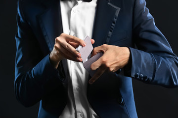 Magician showing tricks with cards on dark background, closeup