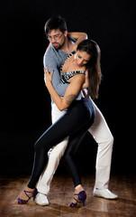 Bailarines de salsa y bachata en poses de baile  con fondo negro