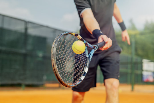 Close up of man playing tennis and beating the ball with a racket.