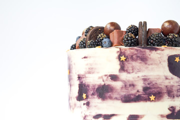 Cake with white and black cream, decorated with blueberries, blackberry, chocolate chip cookies, candies, bars and gold on a white background. Picture for a menu or a confectionery catalog.