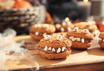Creative cookies prepared for Halloween party on wooden board