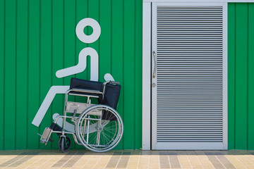 Empty wheelchair standing in a Toilet