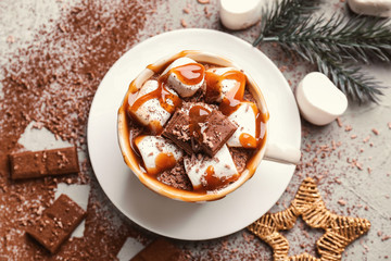 Cup of hot chocolate with marshmallows and caramel on grey table