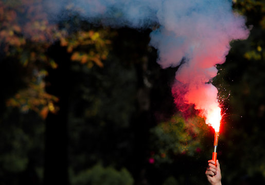 A hand holding bright red light and smoke bomb at the football match outsoors. revolution. concept of protest