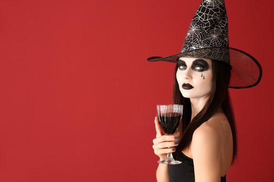 Beautiful woman dressed as witch for Halloween with wine on color background