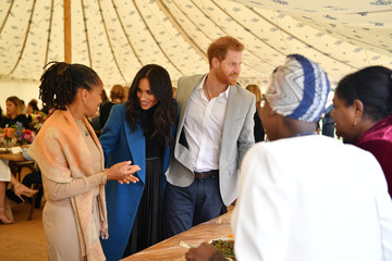 Meghan, Duchess of Sussex, her mother, Doria Ragland and Britain's Prince Harry take part in the launch of a cookbook with recipes from a group of women affected by the Grenfell Tower fire at Kensington Palace in London