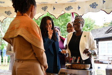 Meghan, Duchess of Sussex jokes with her mother Doria Ragland as she helps to prepare food at the launch of a cookbook with recipes from a group of women affected by the Grenfell Tower fire at Kensington Palace in London