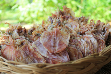 Dried squid in a basket on natural green background