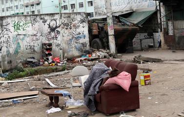 A homeless woman sleeps as Brazilian soldiers patrol during an operation against drug gangs in Jacarezinho slum in Rio de Janeiro