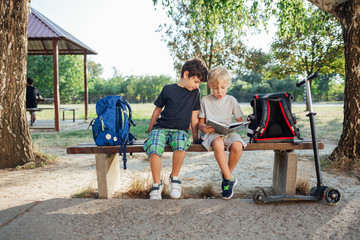 Two boys reading notebook sitting on bench at school
