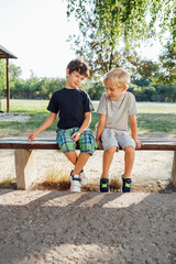 Two boys resting on bench after school