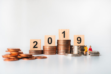 Miniature people, couple woman sitting on golden stack coins with mini house and year 2019 using as business, financial and property concept
