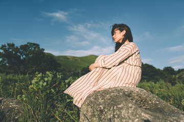 Woman sitting on boulder in field