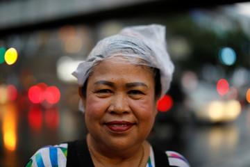 A woman wears a plastic bag on her head to cover it from the rain in Bangkok