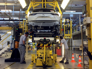 Assembly workers fix the chassis of a DS7 Crossback plug-in hybrid SUV to its body, inside the prototypes workshop at PSA GroupÕs Sochaux plant