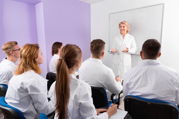 Group of medical students attentively listening to lecture of female teacher in classroom