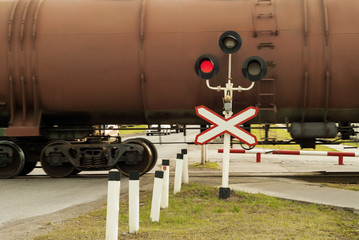 traffic light and sign on the railway crossing during the passage of a freight train with tank wagons