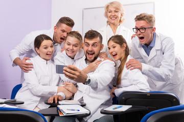 Glad students making selfie indoors