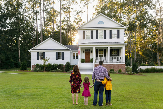 Family of Four With Daughters Looking at Their New Construction White Farmhouse Home