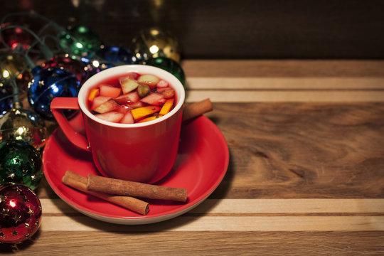 Красная чашка с фруктовым чаем и палочками корицы на блюдце на деревянном фоне