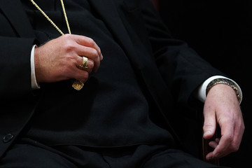 Cardinal Timothy Dolan, Archbishop of New York, holds his necklace during a news conference in Manhattan