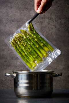 Hand holding asparagus over cooking pot