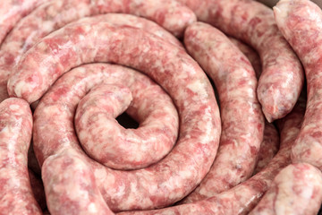 Homemade raw pork sausage on wooden cutting board on black background with garlic and spices.