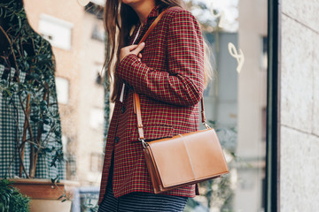 Wall Mural - street style, attractive woman wearing a  mini skirt, check plaid blazer and a lether brown tote bag. fashion outfit perfect for autumn. style of 2018 autumn.