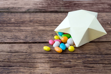 Sweet multicolored candy pills in paper gift box in the shape of yellow star. Sweet magical fairy-tale gift present. Candies, star gift box on wooden rustic background. Top view, flat lay, copy space